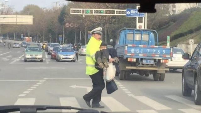 老人艰难过马路,交警暖心