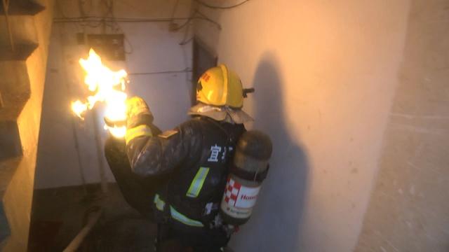 实拍:消防员抱喷火煤气罐走下5楼