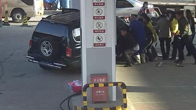 女司机撞倒加油员,众人抬车救人