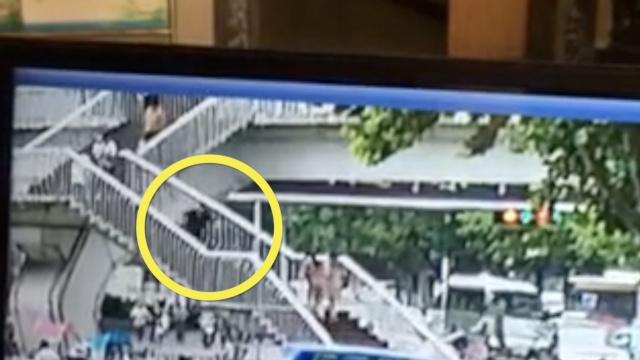 监拍:她失足摔下天桥,疑玩手机所致