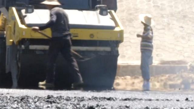 他们160℃沥青中铺路,1天喝25斤水