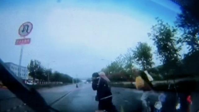 2老人雨中过马路,小车鸣笛却未减速