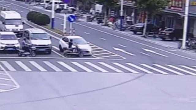 监控:轿车抢黄灯,撞飞闯红灯电动车