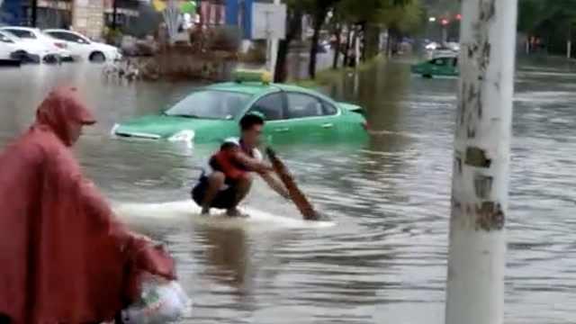 台风袭广东:市民划船上街,蛇游水中