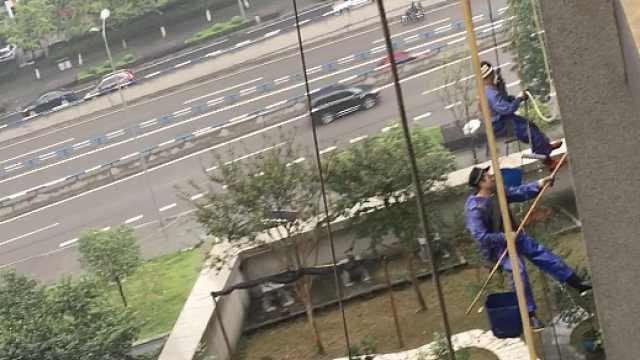 高楼窗外的世界:蜘蛛人雨天洗墙