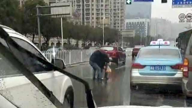 暖心!老人摔倒车流中,的哥下车搀扶