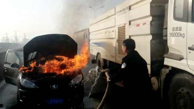 实拍:小车失火,民警借洒水车灭火