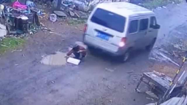 男童蹲地玩耍,面包车倒车卷入车底