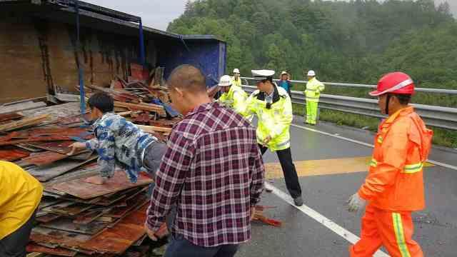 货车侧翻木板堵路,交警司机齐帮忙