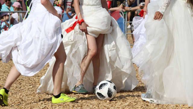 养眼!俄罗斯美女撩起婚纱争抢足球