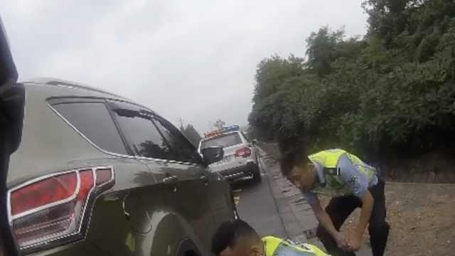 越野车轮胎被扎,交警冒雨帮换胎