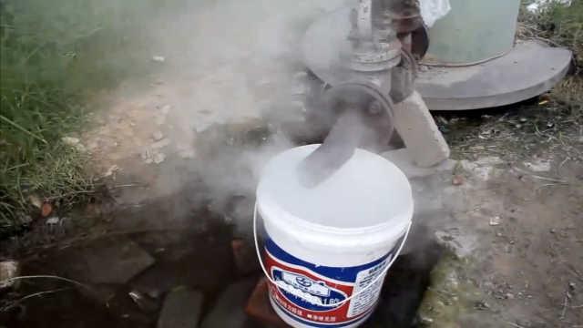 热力管道冒热水,市民排队接水洗澡