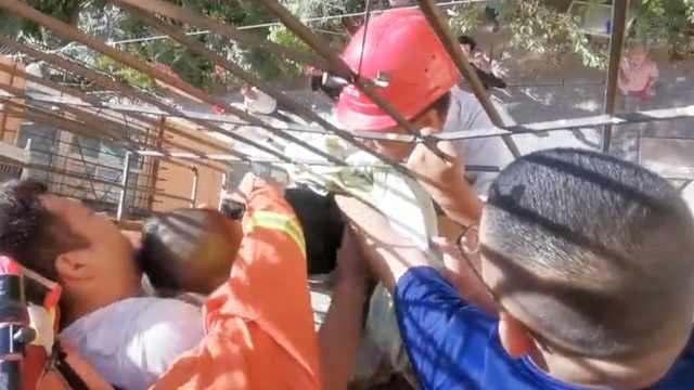 男童头卡护栏悬空,民工站护栏托举