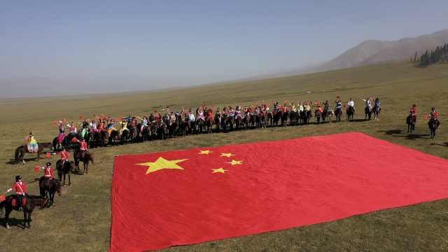 场面喜庆震撼!新疆同胞穿56个民族服饰骑马围巨幅国旗庆国庆