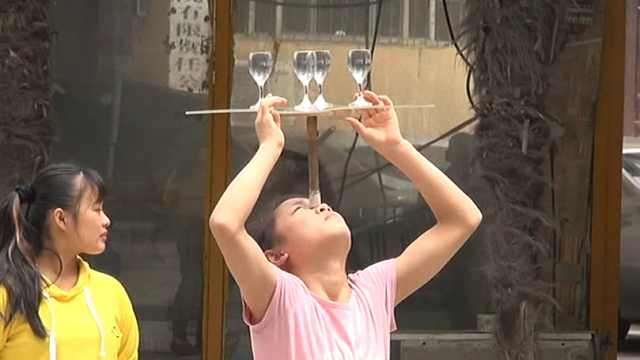 女孩街头耍杂技,头顶玻璃杯引围观