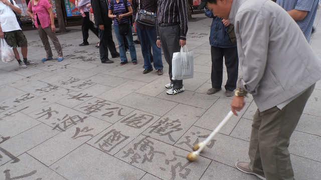 为什么老人总拿大毛笔在地上写字?