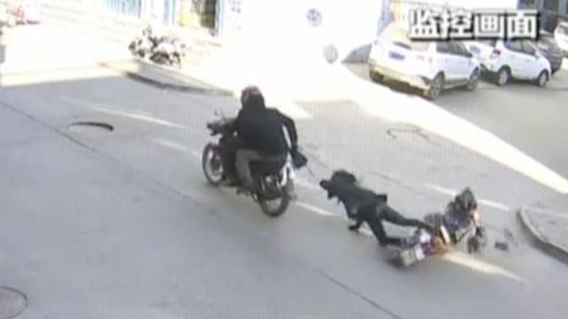两贼飞车夺包,将女子拖行近20米