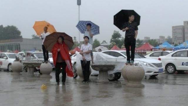 高考场外暴雨如注,家长苦等送伞