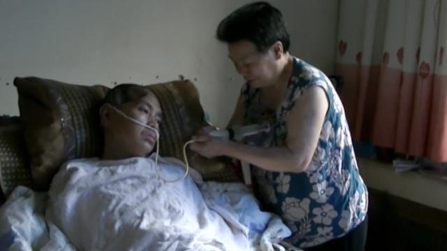 母亲照顾植物人儿17年,注射器喂食
