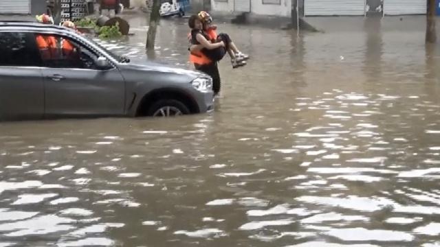 女司机被困洪水,消防蹚水