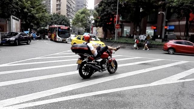 险!摩托停路中,司机躺车上玩手机