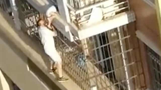 幼童悬高楼情况危急,男子攀爬施救