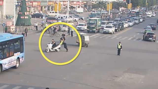 无证男骑无牌摩托闯红灯,刮倒交警