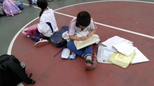 小学生放学等家长,趴满球场写作业