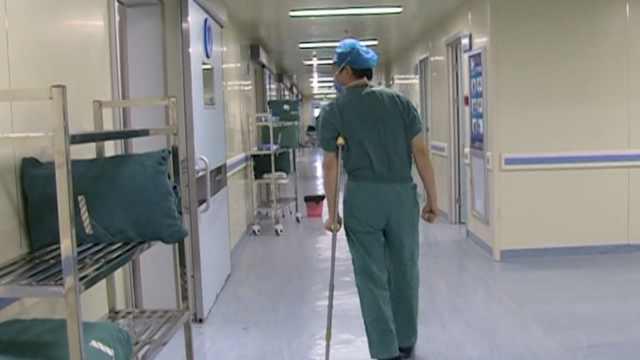 医生摔伤骨折,拄拐杖给病人做手术