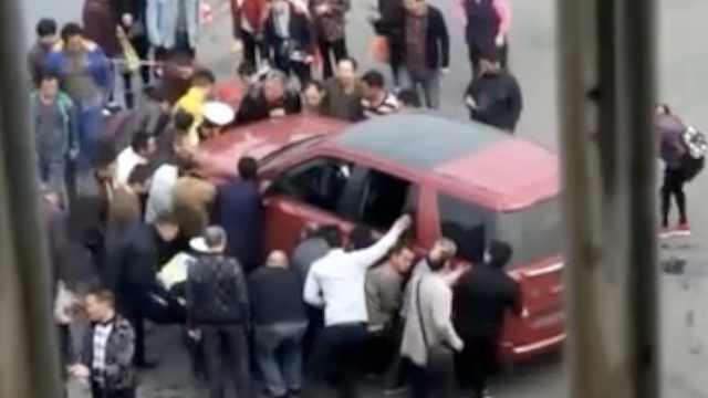 电瓶车司机卷车底,数十人抬车救人