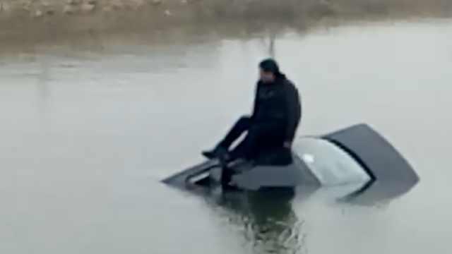 诡异!汽车驶入河中,司机呆坐车顶