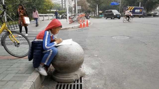 期末作业多,小男生趴路边石墩狂赶