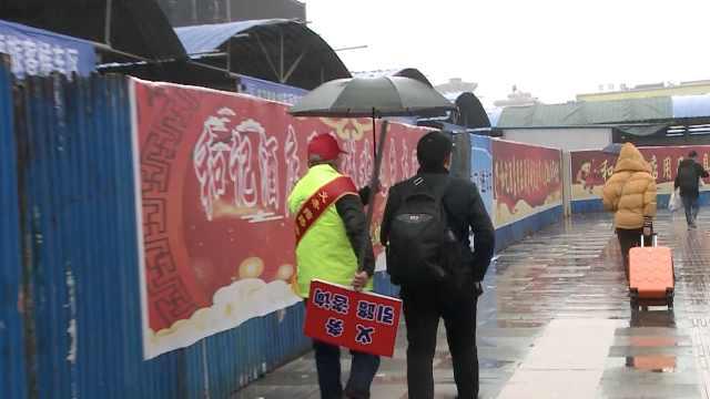 春运的站台:志愿者雨中为旅客撑伞