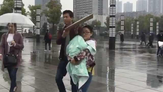 他带娃主城看病,雨中用纸壳护妻儿