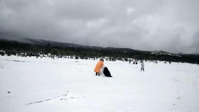 玉龙雪山4月罕见飞雪,游客堆起雪人