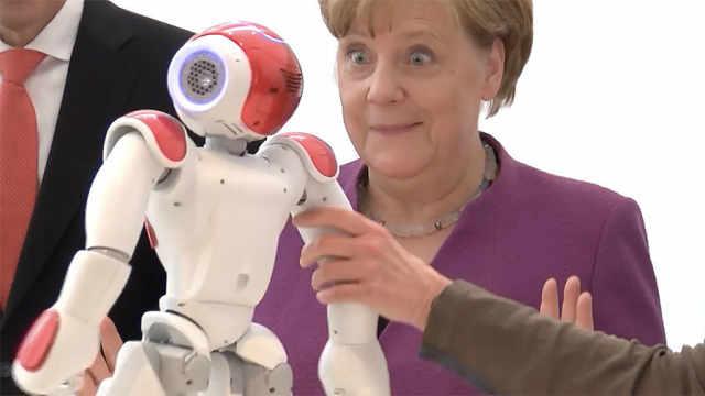 默克尔玩机器人,露出罕见兴奋表情