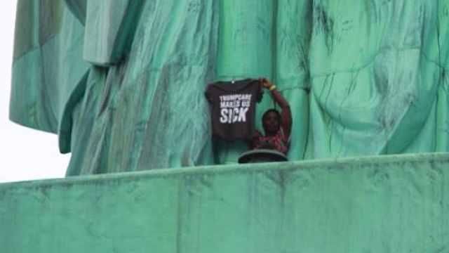 美国女子国庆日爬上自由女神像抗议