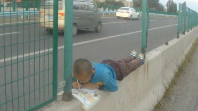 小学生等妈下班,竟趴高速边写作业