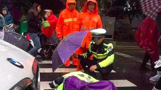 车祸现场,民警脱雨衣帮男子遮雨