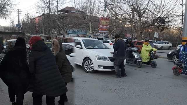 男子拦车要钱横躺路中,被众人抬走