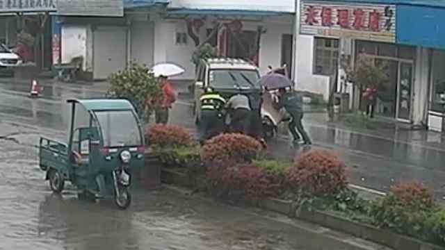 暖!大雨中热心村民与民警齐推车
