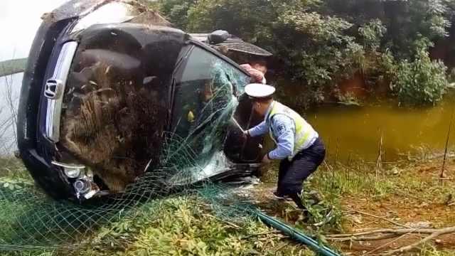 小车侧翻渐落池塘,交警砸玻璃救人