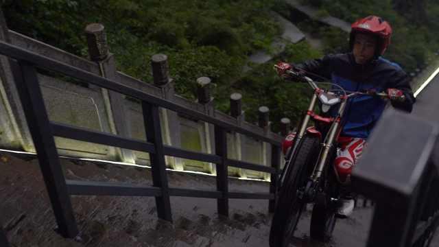 小伙冒雨骑摩托爬天门山999级天梯