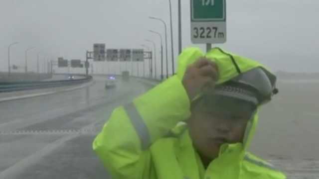 交警桥上播报台风路况,脸被吹变形