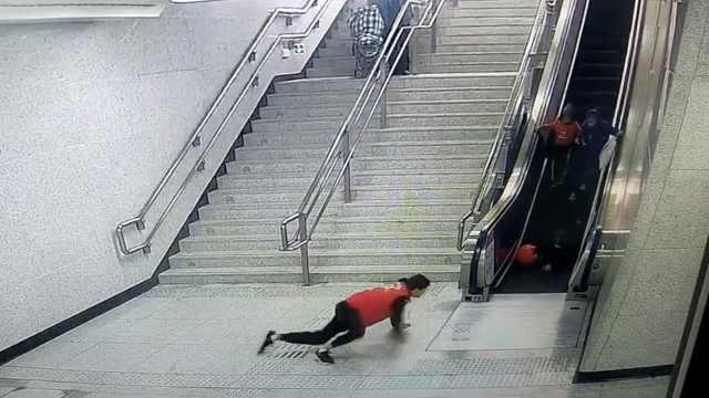 乘客乘电扶梯摔倒,大学生飞扑按停