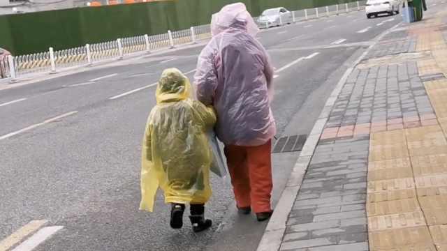 奶奶带娃裹雨衣上街,主动和人隔1米