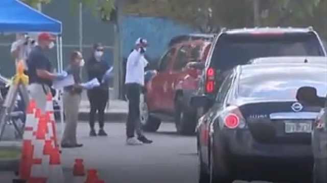 美国迈阿密大批民众排队申领失业救济,警察维持秩序