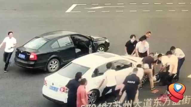 众人抬车救出被压住手臂的男子