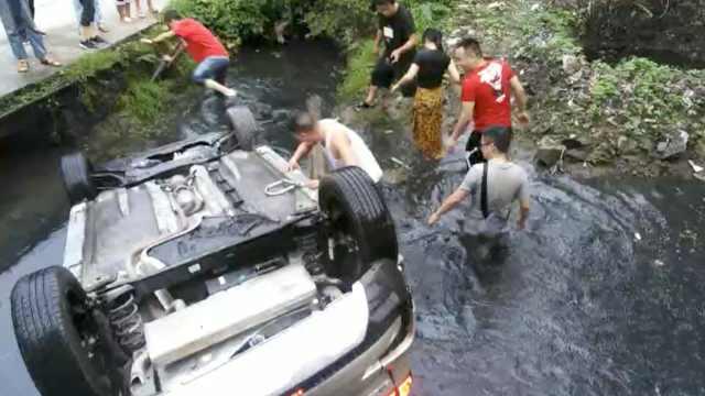 轿车转弯翻下河沟,路人跳水砸窗救出女司机