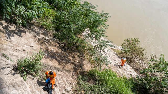 重庆长江岩壁清洁工,顶39℃高温爬30米高岩壁捡